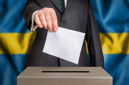 Election in Sweden - voting at the ballot box. The hand of man putting his vote in the ballot box. Flag of Sweden on background.