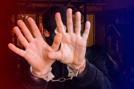 Thief in handcuffs is covering face - police arrested him near crime scene Stock Photo