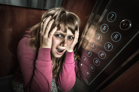 Shocked woman with claustrophobia in the moving modern elevator