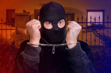 Thief in handcuffs - police arrested him near crime scene