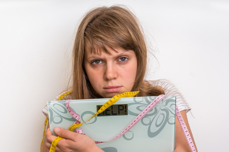 Overweight woman holding digital scales with word HELP! - diet and obesity concept