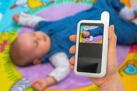 Hand of mother is holding baby monitor camera for safety of her cute baby Stockfoto