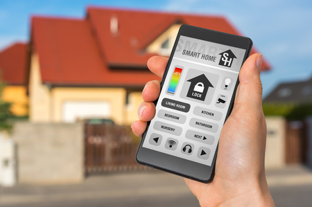 Smart home control app on smartphone with unfocused home in background Zdjęcie Seryjne