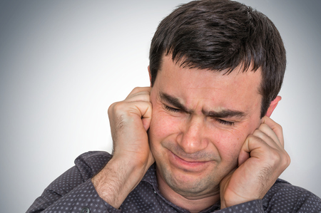 Man covering his ears to protect from loud noise - excessive sound