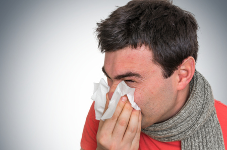 Sick man with flu or cold sneezing into handkerchief - cold and flu concept Standard-Bild - 96485351