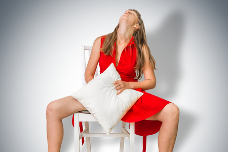 Attractive woman masturbating and playing with herself on chair Standard-Bild