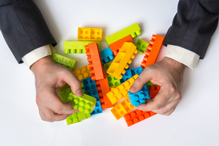 Concept of strategy and reorganization business ideas - young businessman playing with colored toy blocks