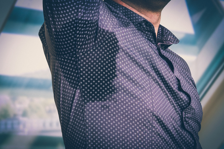 Young man with sweating under armpit in business office - retro style