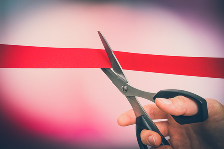 Hand with scissors cutting red ribbon - opening ceremony concept - retro style 写真素材