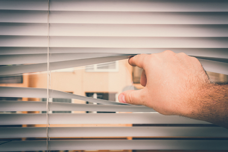 Man is looking out through jalousie, his fingers opening venetian blinds - retro style