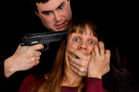Man with a handgun aiming on a head his victim - violence concept