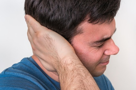 Man with earache is holding his aching ear - body pain concept