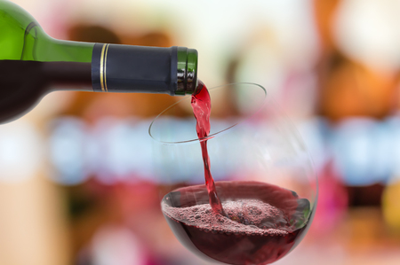 Red wine pouring into a wine glass - celebration concept Stock Photo