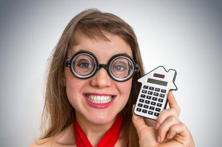 Funny geek or nerd school woman with calculator in her hand Stock Photo