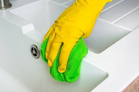Hand in glove with green rag is wiping sink in kitchen - housework and housekeeping concept Stock Photo