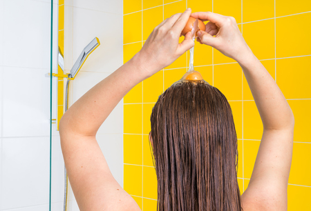 Attractive woman applying egg conditioner on her hair in bathroom Imagens