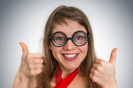 Young funny geek or nerd woman isolated on gray background Stock Photo