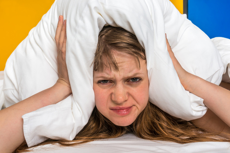 Attractive woman in bed covering ears with pillow because of noise - insomnia concept