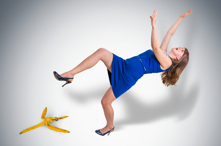 Business woman slipping and falling from a banana peel - business risk concept Foto de archivo