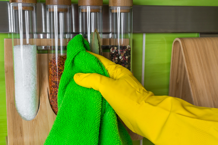 Hand in glove with green rag is wiping spice bottles - housework and housekeeping concept Banque d'images