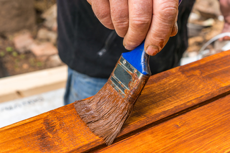Painter with paintbrush painting wooden surface for protection wood from external influences