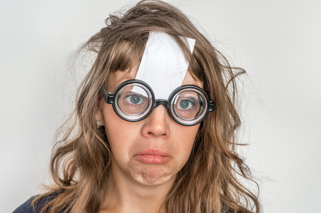 Portrait of a funny woman with blank white sticky paper over her forehead Banque d'images