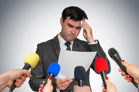 Nervöser Mann schwitzt, er hat Angst vor öffentlicher Rede. Viele Mikrofone herum.