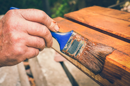 Painter with paintbrush painting wooden surface for protection wood from external influences - retro style