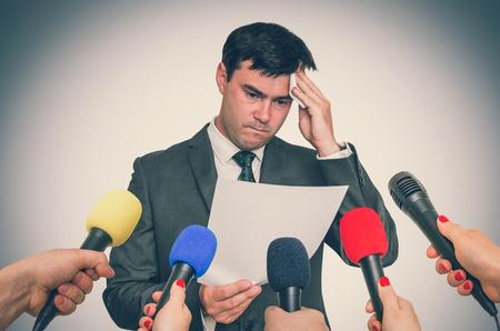 Nervöser Mann schwitzt, er hat Angst vor öffentlicher Rede. Viele Mikrofone herum. Retro-Stil.