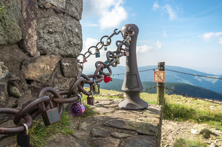 A lot of love padlocks on chain on the top of mountain - romantic concept of love