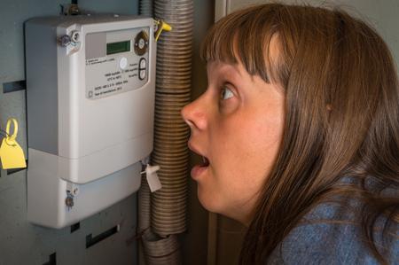 Mujer aterrorizada está comprobando el medidor de electricidad: consumo y concepto de electricidad costosa