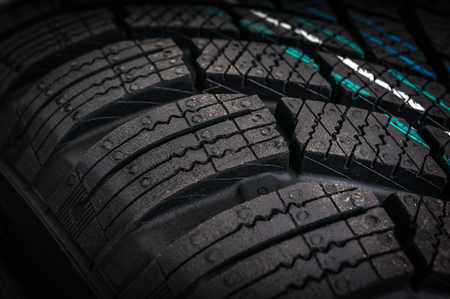 Winter car tires in row isolated on black background