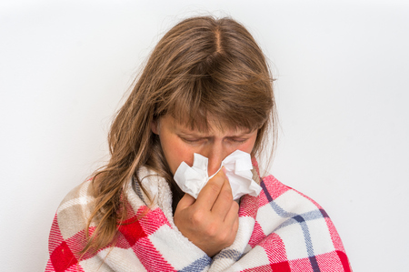 Sick woman with flu or cold sneezing into handkerchief - cold and flu concept Фото со стока