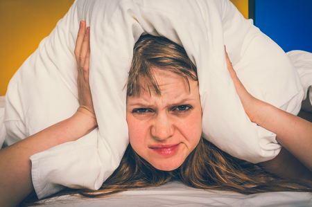Attractive woman in bed covering ears with pillow because of noise - insomnia concept - retro style