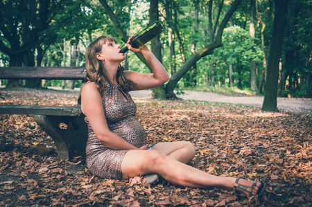 Pregnant woman drinking wine in the park - alcohol addiction - retro style Stock Photo