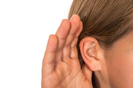 La femme écoute avec sa main sur une oreille - concept de perte auditive Banque d'images