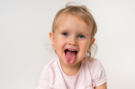 Little baby girl showing tongue on isolated background
