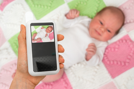 Hand of mother is holding baby monitor camera for safety of her cute baby 免版税图像