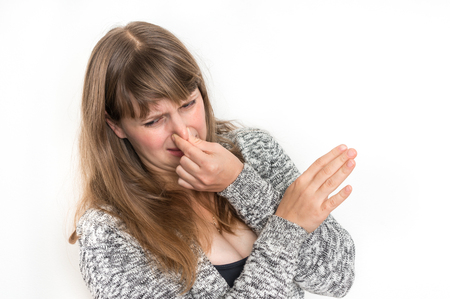 Pretty woman is holding her nose - bad smell concept Imagens