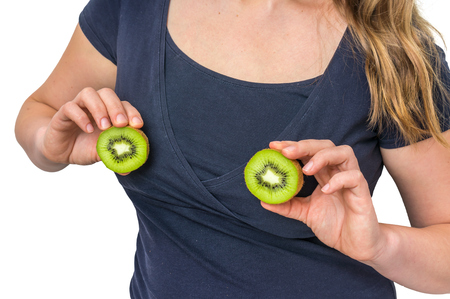Beautiful woman holds kiwi in hands above her breast - plastic surgery and silicone implants concept Stock Photo