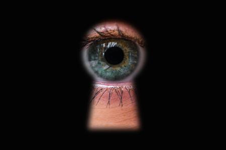 Ojo humano detrás de la puerta mirando a través de un ojo de la cerradura - concepto de voyeurismo