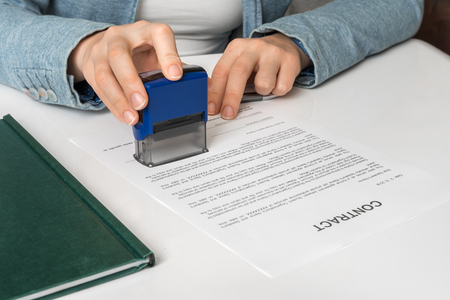 Business woman putting stamp on documents in the office - signing contract concept Banque d'images - 118081911