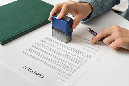 Business woman putting stamp on documents in the office - signing contract concept Banque d'images - 118082301