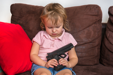 Child is playing with parents gun - safety and accident concept 版權商用圖片