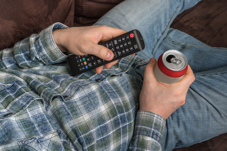 Young guy is lying on sofa with TV remote control and drinking beer - resting concept Imagens