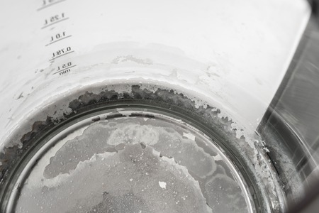Limescale at the bottom of kettle - hard water and calcium concept