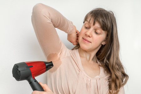 Woman with sweating under armpit is drying her armpit with hair dryer Stockfoto - 120040456