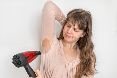 Woman with sweating under armpit is drying her armpit with hair dryer Stockfoto - 121427076