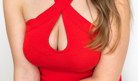 Sexy woman with beautiful big breasts in red dress isolated on white