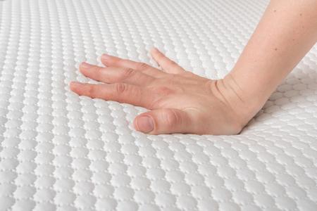 Vrouw kiest nieuwe matras voor goed slapen. De hand van de vrouw test de kwaliteit van de matras.